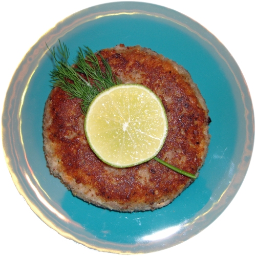 Salmon and potato fishcake, shown with a slice of lime and a frond of dill.