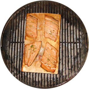 Sea trout fillets cooked on a barbecue 'grilling plank'.