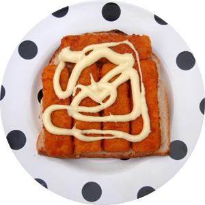 A fish finger [fish stick] sandwich with salad cream